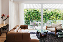 Leather sofa, armchair and coffee table with glass top in front of window