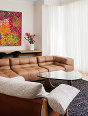 Leather sofa and coffee table with glass top in front of window with floor-length curtain