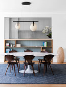 Oval dining table with designer chairs in front of an open shelf