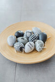 Easter eggs hand-painted in shades of grey on wooden plate