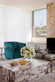 Bouquet of flowers on marble coffee table, turquoise armchair in front of window in living room