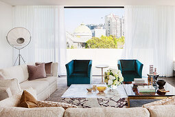 Marble coffee table next to ebony and brass coffee table, elegant sofa set and turquoise armchair in front of window in penthouse apartment