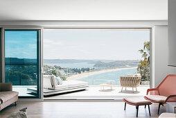 Blick durch geöffnete Schiebetür auf Terrasse mit Daybed, Beistelltisch und Clubsessel und auf das Meer