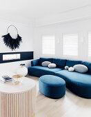 Blaue Sofagarnitur mit Polsterhocker in hellem Wohnzimmer