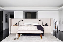 Double bed and custom-made headboard with storage space, clothes bench and silk carpet in an elegant bedroom