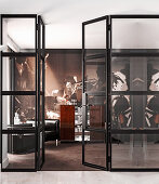View through glass door into house bar with bar counter, leather armchairs and designer wallpaper