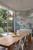 Long wooden table and chairs in front of mural wallpaper and next to terrace doors