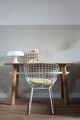 Schreibtisch mit Tischleuchte und Keramik-Häuschen und Klassikerstuhl vor hellgrauer Wand