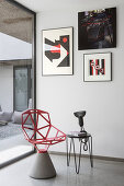 Red designer chair with cement pedestal and side table below modern artworks on wall