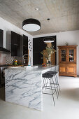 Marble island counter and classic barstools below concrete ceiling