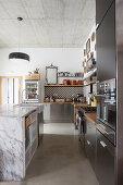 Schwarze Einbauküche mit Marmor-Kücheninsel unter Betondecke