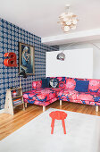 Pink, patterned sofa and blue wallpaper in living room