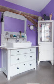 Sink on old chest of drawers and corner cabinet in purple bathroom