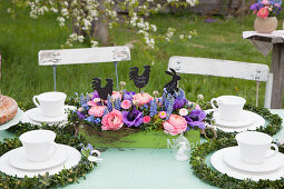 Table festively set for afternoon coffee with luxuriant Easter flower arrangement