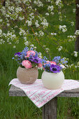 Spring flowers in spherical vases in garden