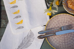 Linen napkins printed with feathers on Easter table