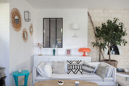 Scatter cushions on white couch in front of sideboard and potted tree