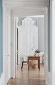 Blick durch Flur auf Schreibtisch vor eleganter, weißer Flügeltür in renovierter Altbauwohnung