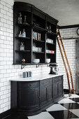 Black painted dresser made from repurposed bookcase on tiled wall in black and white kitchen