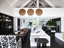 Offener Wohnraum in Schwarz und Weiß, mit Polstersofa, Couchtisch und Regalschrank, im Hintergrund Küche und Treppenaufgang