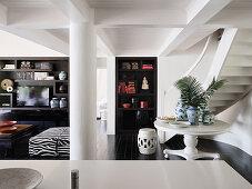 Blick über Küchentheke auf rundem Tisch, Treppenaufgang und Regalschrank