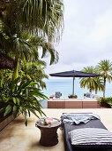 Outdoorbett und Beistelltisch auf Terrasse mit Meerblick