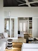 Wohnzimmer mit weißer Polstergarnitur und schwarz-weißem Beistelltisch, Blick durch geöffnete Flügeltüren ins Schlafzimmer