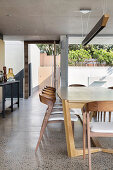 Modern wooden chairs at dining table in architect-designed house with concrete ceiling