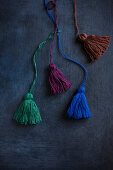 Hand-made tassels in various colours on black surface