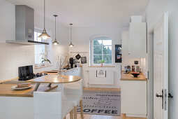 Weiße Küche mit halbrunder Frühstückstheke an Küchenzeile und Barhockern in umgebauter Molkerei