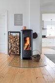 Kaminofen mit brennedem Feuer, daneben Holzlager im Wohnzimmer, im Hintergrund Blick in die Küche