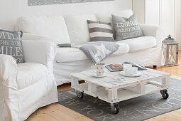 Sitzmöbel mit weißen Hussen und Paletten-Couchtisch im Wohnzimmer, in umgebauter Molkerei
