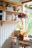Storage baskets on wooden shelves above desk