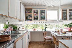 Ribbon windows along two walls in cosy, white kitchen-dining room