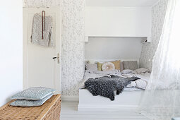 Bed in niche under sloping ceiling in white bedroom