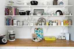 Crockery and kitchen utensils on three shelves above worksurface