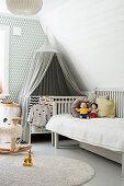 Grey canopy above cot in child's bedroom in grey and white
