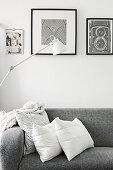 Graues Polstersofa mit Kissen unter schwarz-weißen Bildern und Stehlampe