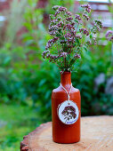 Flowering oregano in clay bottle with tag made from wooden disc