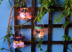 Handmade candle lanterns decorated with lavender hung from trellis