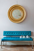 Round gilt-framed mirror above tea service on bright blue couch