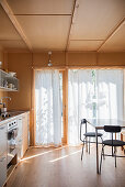 Wood-clad kitchen with white curtains on terrace windows
