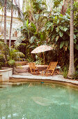 Pool, deck chairs and parasol in the garden with exotic plants