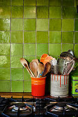 Cooking utensils in ceramic pots and painted tin cans