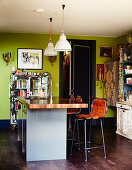 Colourful mixture of files in kitchen-dining room with green walls