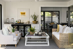 Wohnliche, überdachte Terrasse mit Sitzmöbeln, Couchtisch und Hausbar