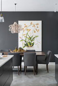 Dining table with grey upholstered chairs, picture with botanical motif on grey wall