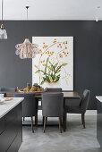 Esstisch mit grauen Polsterstühlen, Bild mit botanischem Motiv an grauer Wand