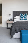 Double bed and bedside table against finely striped wallpaper in bedroom