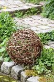 Woven ball of vine tendrils on garden path